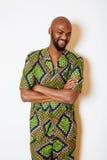 Stående av ungt stiligt afrikanskt bära för man som är ljust - grön nationell dräkt som ler att göra en gest royaltyfri fotografi