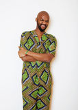 Stående av ungt stiligt afrikanskt bära för man som är ljust - grön nationell dräkt som ler att göra en gest arkivfoton