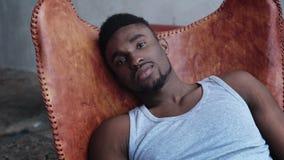 Stående av ungt stiligt afrikanskt mansammanträde på läderstolen och att se kameran Allvarlig modellman arkivfilmer
