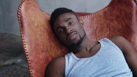 Stående av ungt stiligt afrikanskt mansammanträde på läderstolen och att se kameran Allvarlig modellman arkivfoton