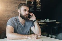 Stående av ungt stiligt skäggigt hipstermansammanträde i kafé på tabellen och samtal på hans mobiltelefon Telefon royaltyfri bild