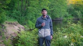 Stående av ungt turist- mandricksvatten i skogen nära floden som är utomhus- arkivfilmer