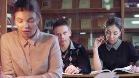 Stående av universitetflickan i arkivet som förbereder hennes forskning och andra studenter i bakgrunden arkivfilmer
