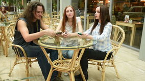 Stående av uttråkade vänner som sitter i kafé medan hennes flickvänner som använder smartphones lager videofilmer