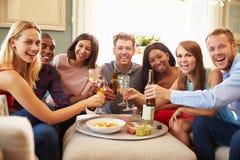 Stående av vänner som firar med ett hemmastatt rostat bröd royaltyfri fotografi