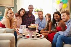 Stående av vänner som hemma firar födelsedag arkivfoton