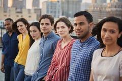 Stående av vänner som samlas på takterrassen för parti med stadshorisont i bakgrund fotografering för bildbyråer