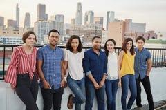 Stående av vänner som samlas på takterrassen för parti med stadshorisont i bakgrund royaltyfria bilder