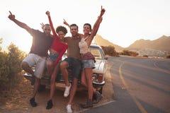 Stående av vänner som står bredvid den klassiska bilen royaltyfri foto