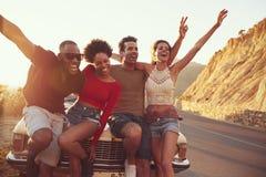 Stående av vänner som står bredvid den klassiska bilen arkivfoton