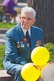 Stående av veteran för världskrig II med ballonger i Volgograd Arkivfoto