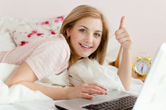 Stående av visningtummen upp härlig försiktig söt ung kvinna i säng med bärbar datorPCdatoren som ser kameran Royaltyfria Bilder