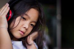 Stående bärande hörlurar för flicka, lyckligt som lyssnar till musik Arkivbilder