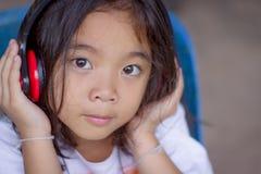 Stående bärande hörlurar för flicka, lyckligt som lyssnar till musik Royaltyfri Bild