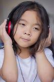 Stående bärande hörlurar för flicka, lyckligt som lyssnar till musik Royaltyfri Fotografi