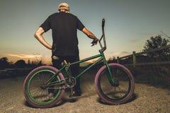 Stående bmxcykel för ung man BMX-ryttare med och en solnedgång royaltyfri fotografi
