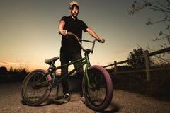 Stående bmxcykel för ung man BMX-ryttare med och en solnedgång arkivbilder