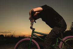 Stående bmxcykel för ung man BMX-ryttare med och en solnedgång fotografering för bildbyråer