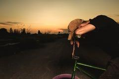 Stående bmxcykel för ung man BMX-ryttare med och en solnedgång royaltyfri bild