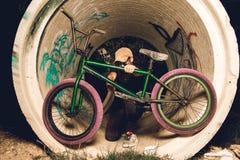 Stående bmxcykel för ung man BMX-ryttare med och en solnedgång arkivfoton