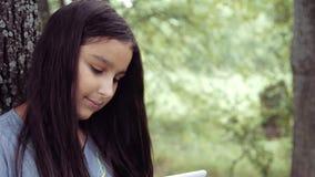 Stående Den härliga flickan använder en minnestavla på naturanseende vid ett träd i soligt väder och skrattar lager videofilmer