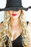 Stående Den härliga unga blonda kvinnan i svart hatt med urringningen på en vit bakgrund ler hemskt royaltyfria bilder