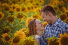 Stående det fria för förälskelsepar i solrosfält Arkivfoto