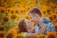 Stående det fria för förälskelsepar i solrosfält Royaltyfri Fotografi
