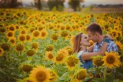 Stående det fria för förälskelsepar i solrosfält Arkivfoton