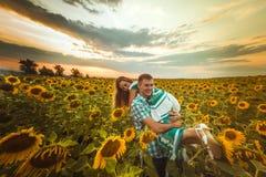Stående det fria för förälskelsepar i solrosfält Royaltyfria Bilder