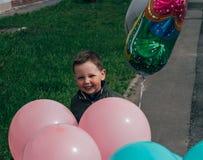 Stående en pojke med rosa och blåa ballonger, med fjärilar arkivbild
