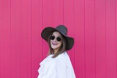 Stående en ung härlig kvinna med hatten och solglasögon över beträffande royaltyfri foto