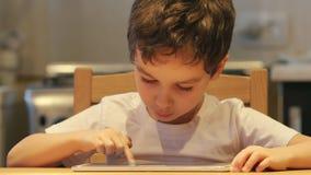 STÅENDE: Ett gulligt litet barn använder en minnestavlaPC på en tabell hemma Kläder: vit skjorta lager videofilmer