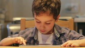STÅENDE: Ett gulligt litet barn använder en minnestavlaPC på en tabell hemma Tillfällig kläder arkivfilmer