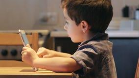 STÅENDE: Ett gulligt litet barn använder en minnestavlaPC på en tabell hemma Tillfällig kläder Slapp fokus lager videofilmer