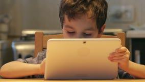 STÅENDE: Ett gulligt litet barn rymmer på händer en vitminnestavlaPC på en hemmastadd tabell Tillfällig kläder arkivfilmer