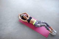 Stående för bästa sikt av en ung kvinna som ligger på den matta yogan Royaltyfri Bild
