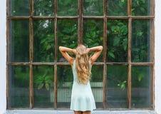 Stående för bakre sikt av den unga romantiska kvinnan i en botanisk trädgård Royaltyfria Bilder