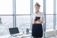 Stående för bakre sikt av en ung kvinnlig kontorsarbetare som använder apps på hennes minnestavladator, bärande formell dräkt som arkivbild