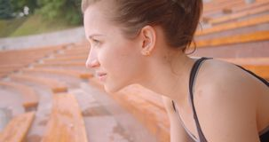 Stående för Closeupsidosikt av den unga caucasian sportiga kvinnliga joggeren som ser kameran med beslutsamhet som sitter på stock video