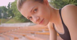 Stående för Closeupsidosikt av den unga caucasian sportiga kvinnliga joggeren som tröttas se kameran med beslutsamhet arkivfilmer