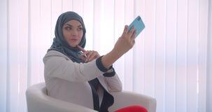 Stående för Closeupsidosikt av den unga muslim attraktiva kvinnliga doktorn i hijab och det vita laget som tar selfies på telefon lager videofilmer