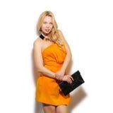 Stående för flicka för modemodell i orange klänning och modern accessori Arkivbild
