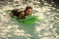 Stående för högt mode av den eleganta kvinnan Härlig kvinna i vatten med den gröna uppblåsbara krokodilen royaltyfria foton