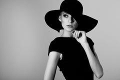 Stående för högt mode av den eleganta kvinnan i den svartvita hatten royaltyfri fotografi