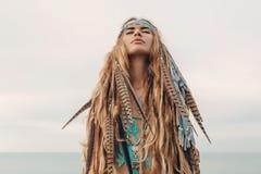 stående för modemodell utomhus ung kvinna för bohostil med huvudbonaden som göras av fjädrar arkivfoto