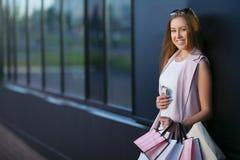 Stående för modeshoppingflicka Le flickan med shoppingpåsar med telefonen i hand Begrepp av kvinnashopping Arkivfoto
