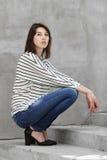 Stående för naturligt ljus utomhus av den praktiserande modellen för ung trendig brunettkvinna som utomhus poserar mot stads- sti arkivfoton