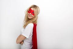 Stående för sidosikt av den säkra kvinnan i superhero mot vit bakgrund arkivfoton