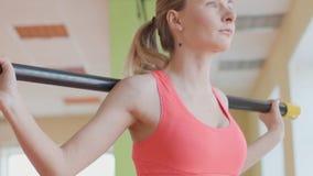 Stående för sidosikt av en ung kvinna som gör squats på konditionidrottshallen lager videofilmer